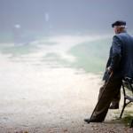 Äldre man som vilar mot en parkbänk
