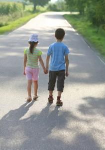 Mindre barn går på en väg och håller handen