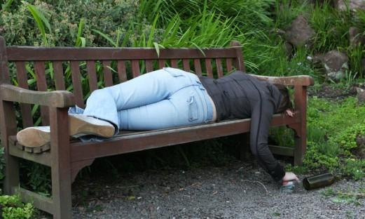 Ung berusad person sover på en parkbänk med en spritflaska bredvid