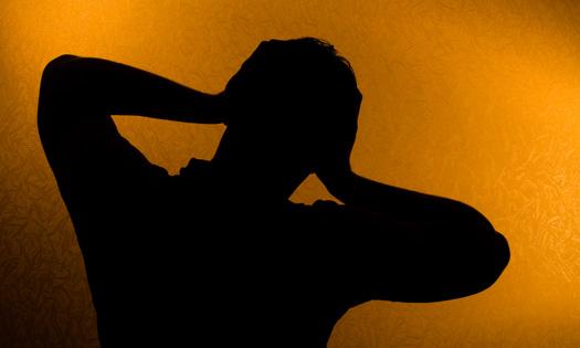 siluett av man som håller sig om huvudet