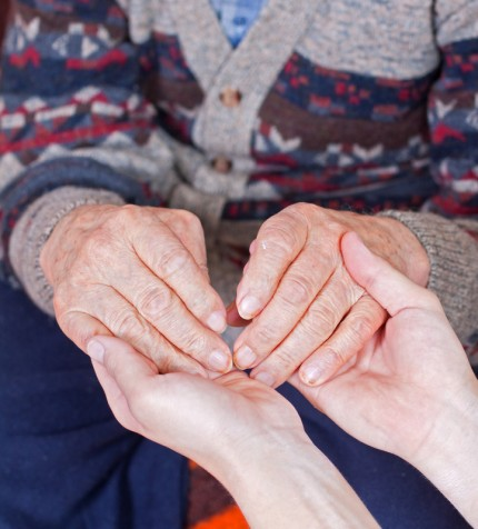 En yngre håller en äldre persons händer