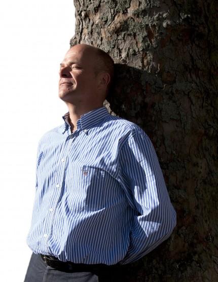 Man står lutad mot träd och solar