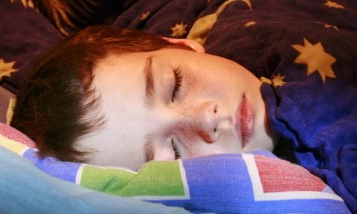 Pojke som sover i sin säng
