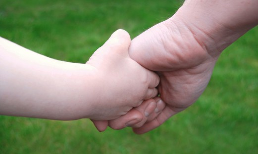 närbild på vuxens hand som håller ett barn i handen