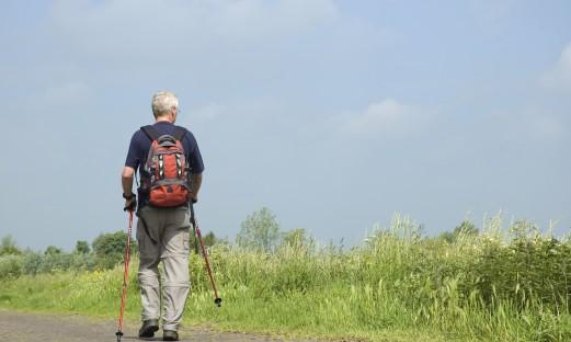 man som är ute och går med ryggsäck och gångstavar på landsväg
