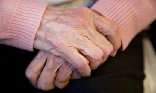 En äldre kvinnas korsade händer