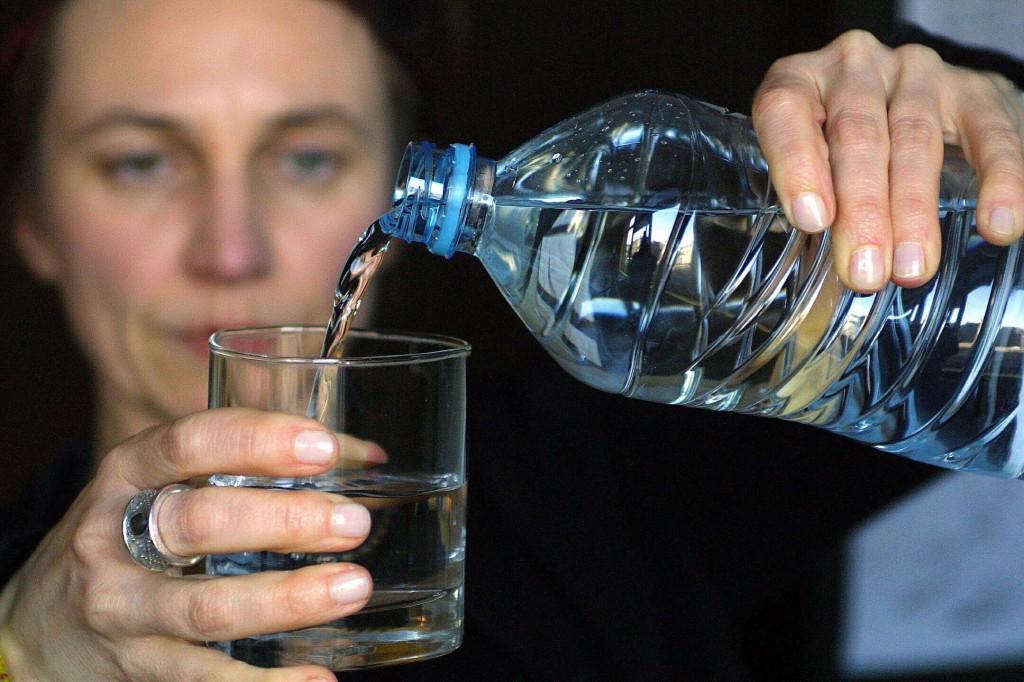Kvinna håller glas och vattenflaska