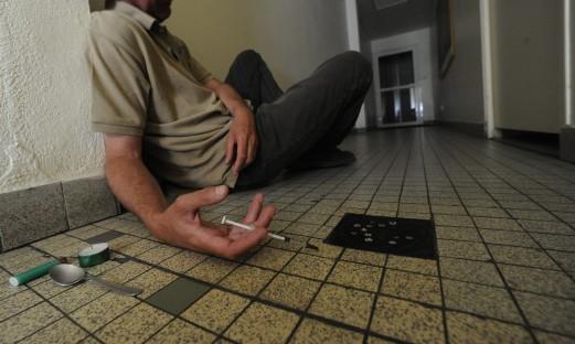 Missbrukare ligger på golvet med spruta
