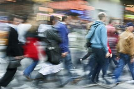 Suddig bil av människor i rörelse på trottoar