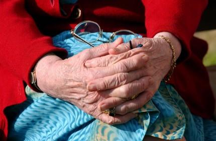 äldre med händerna i knät