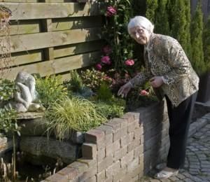 Äldre kvinna i sin trädgård.