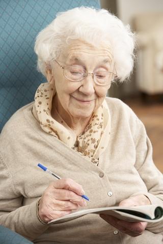äldre dam löser korsord