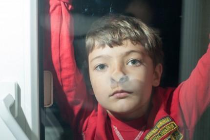 pojke som tittar ut genom ett fönster