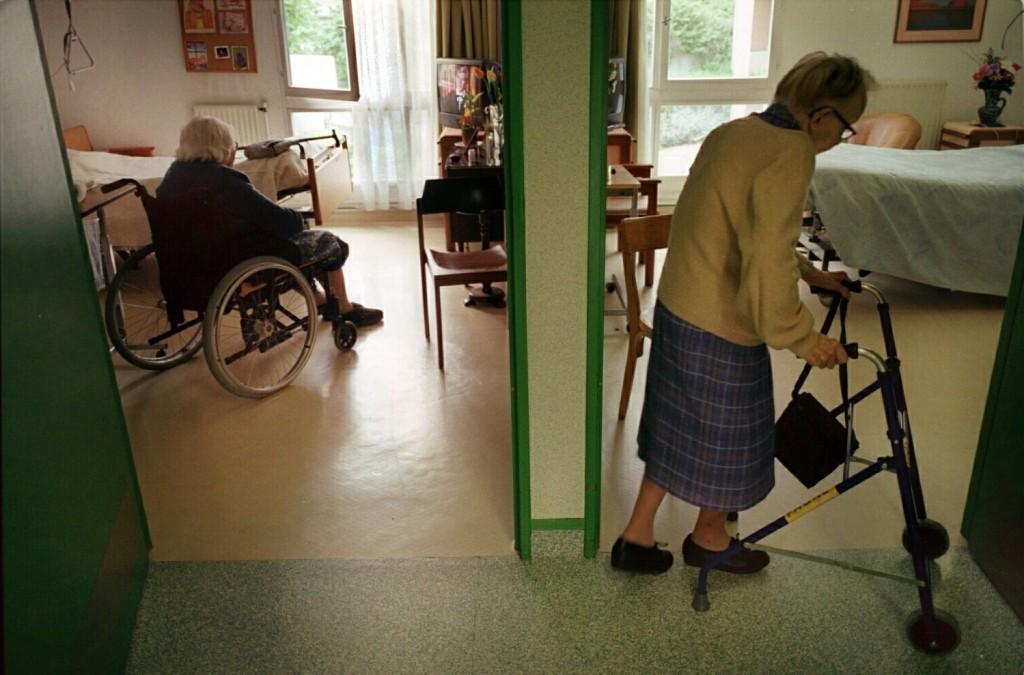 I förgrunden ses en äldre kvinna gå med rollator i en korridor. I bakgrunden ses en annan äldre person sitta i en rullstol