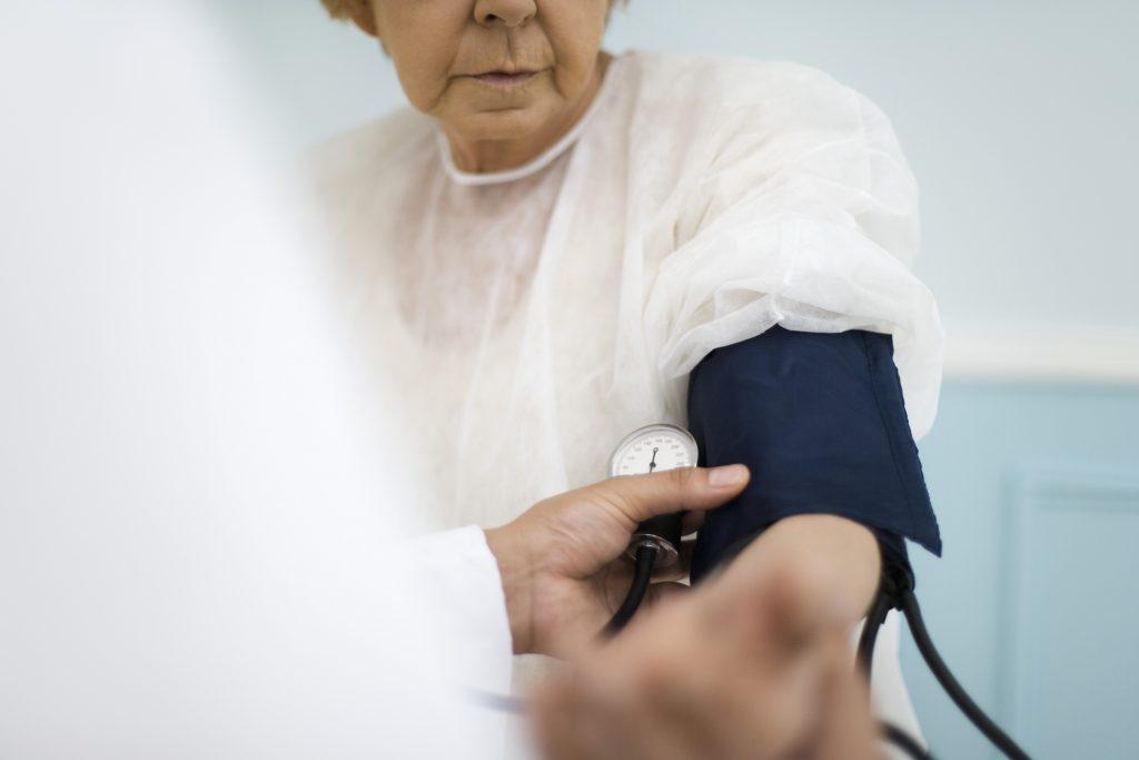 Bilden visar hur en patient, en äldre kvinna klädd i vit blus får sitt blodtryck mätt. en blå blodtrycksmanschett sitter på hennes vänstra arn