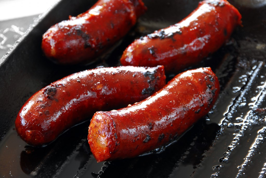 appetizing red roast sausages on frying pan