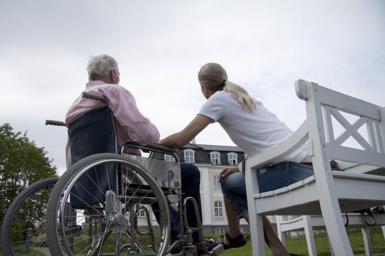 äldre man i rullsol pratar med kvinna_COLOURBOX1178224