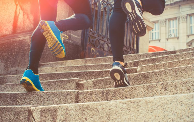 Couple wearing sportswear and jogging on steps in city.