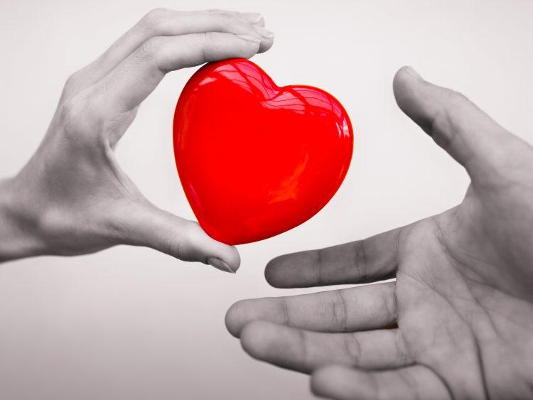 bilden visar två händer, en som håller i ett rött stiliserat hjärta och är på väg att lämna över till den andra handen.