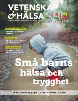 Omslagsbild till temanummer om små barns hälsa och trygghet. På bilden ses ett litet barn klätt i grå mjukiskläder och röda gummistövlar. Barnet står i en vattenpöl på en skogsväg och undersöker något som det hittat i vattnet