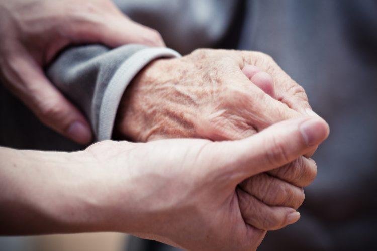 en rynkig hand som tillhör en äldre person hålls om av ett par yngre händer