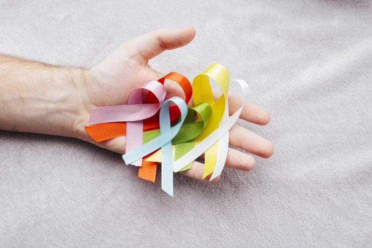 Bild på hand som håller band i olika färger som alla representerar olika cancertyper.