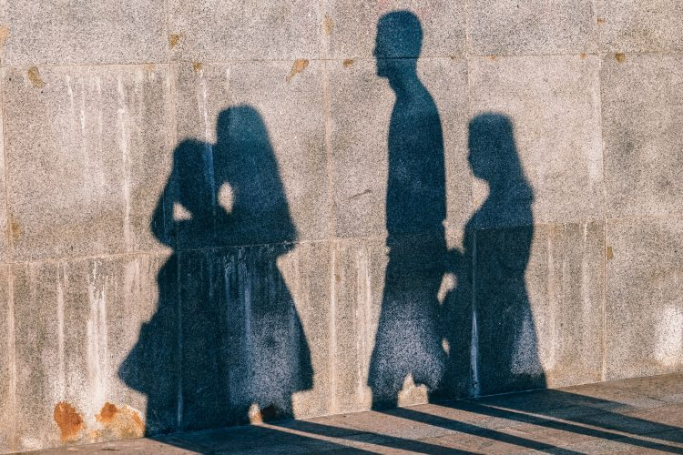 Bilden föreställer skuggor av flera personer som avtecknar sig mot en stenvägg
