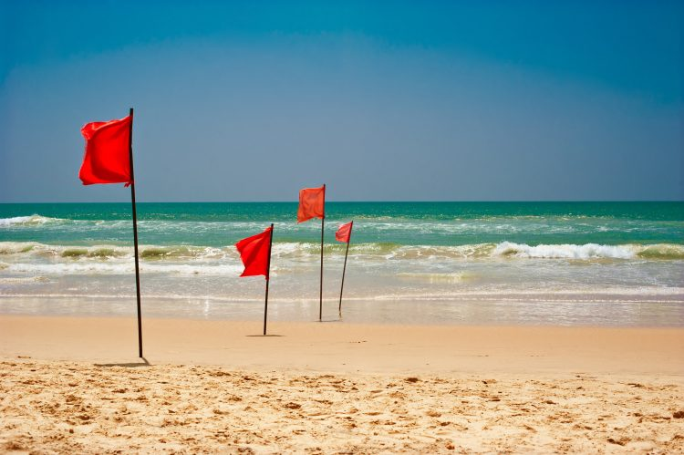 Röda varningsflaggor som varnar för starka vågor.