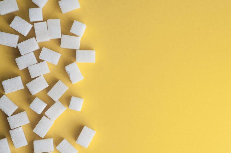 bilden föreställer sockerbitar på ett gult underlag