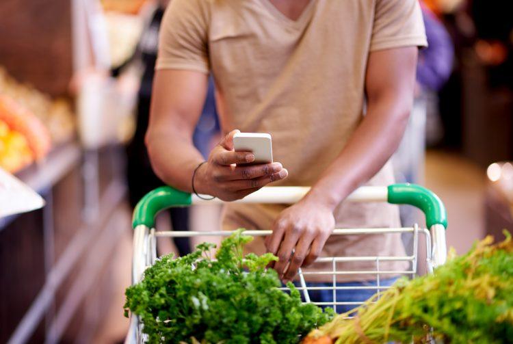 person som stödjer sig över en kundvagn full med mat och tittar i sin smartphone