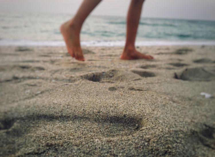 fötter på en person som går på en sandstrand och lämnar spår efter sig