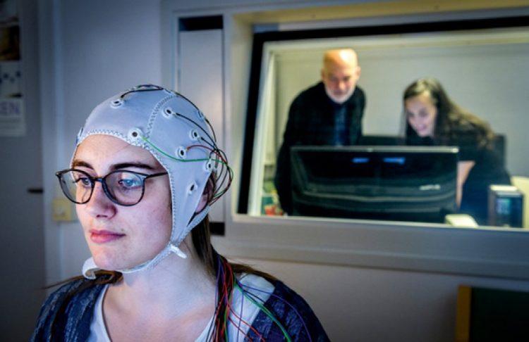 Bilden föreställer Osa Abendroth iklädd elektrodmössa. Hon sitter framför en datorskärm. Forskarna Inês Bramão och Mikael Johansson övervakar vid en skärm i rummet bredvid.