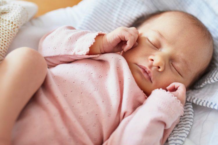 sovande nyfödd baby i rosa kläder