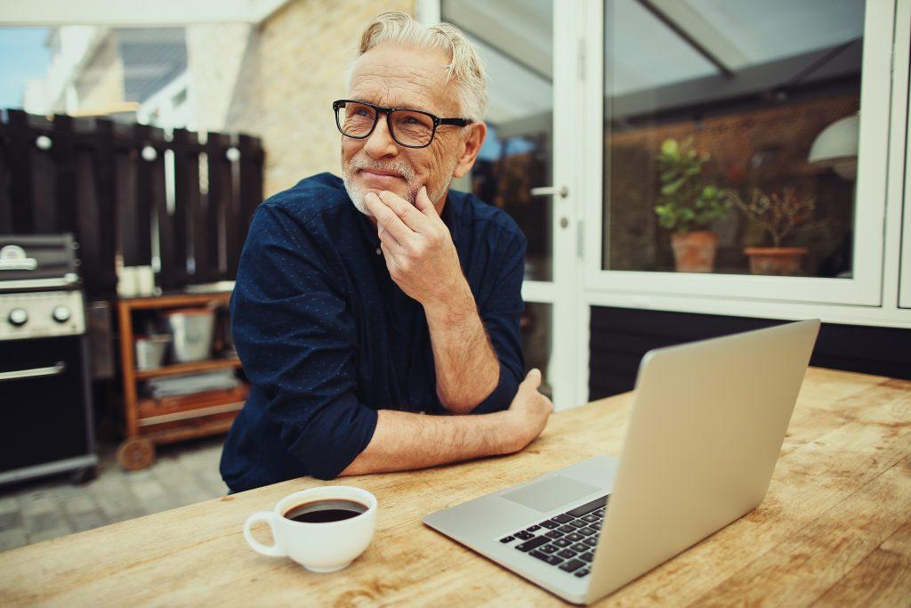 leende äldre man sitter vid bord med en laptop framför sig och en kopp kaffe