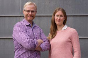 Blond man i lila skjorta och kvinna med långt brunt hår mot grå vägg.