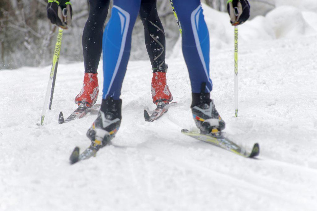 Stavar och två par ben av skidåkare i snö.