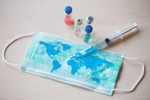 bilden visar ett munskydd som ligger på ett bord. Munskyddet är illustrerat med en världskarta. Över munskyddet ligger en spruta och bredvid några små glasflaskor