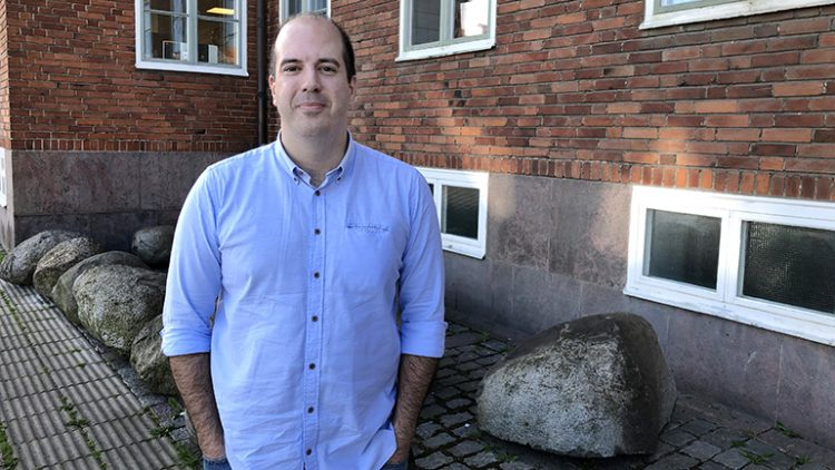 Bilden föreställer Bruno Chrcanovic, han står ute framför ett tegelhus och är klädd i blå skjorta