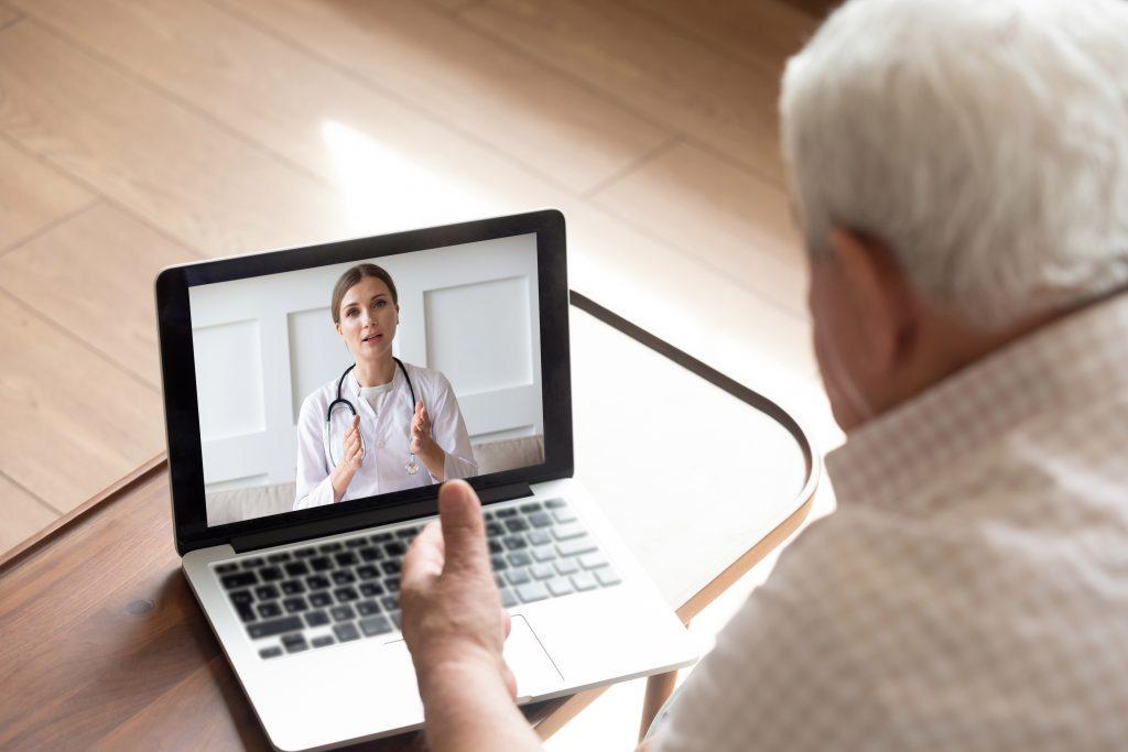 På bilden ses en äldre man bakifrån. Framför sig på har han en laptop och på skärmen syns en kvinna, klädd i vita kläder och ett stetoskop runt halsen. Det ser ut som att mannen och kvinnan pratar med varandra.