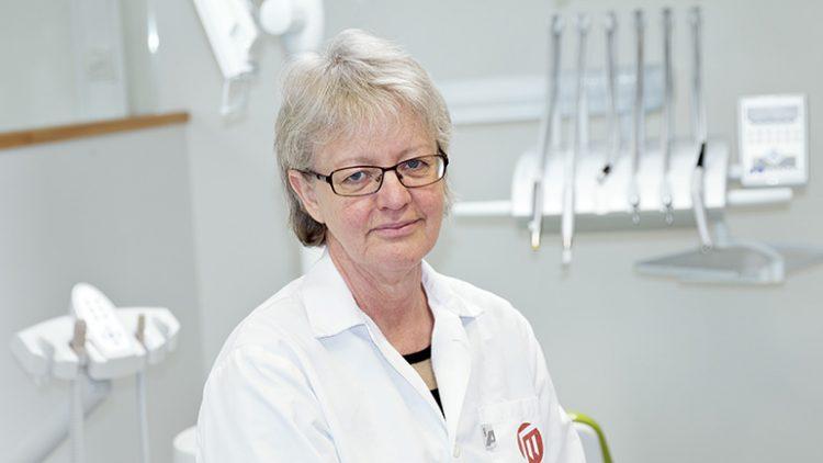 Bilden föreställer Eva Wolf. Hon är klädd i vit rock och i bakgrunden syns en uppsättning tandläkarborrar
