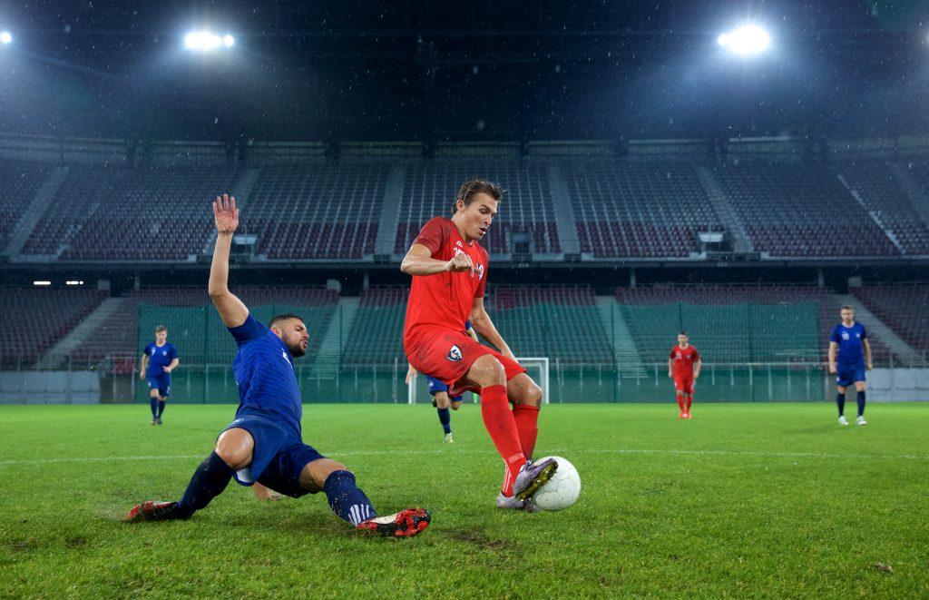 På bilden ses två fotbollsspelare som kämpar om bollen. I bakgrunden syns tomma läktare
