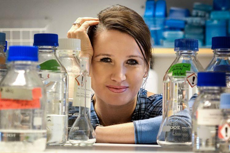 På bilden ses Kinga Gawlik. Bilden är tagen på hennes labb och man ser Kinga som lutar sig mot en hylla omgiven av olika labb-flaskor