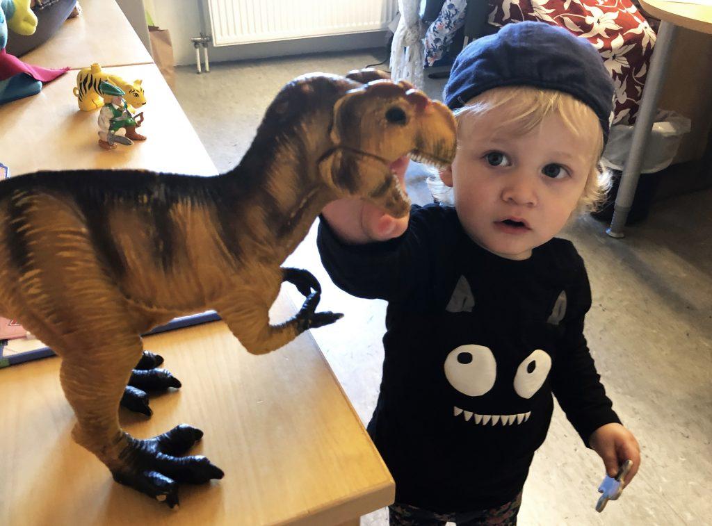 Bilden föreställer Love, en liten pojke iklädd en svart tröja med vita ögon och tänder på magen och en keps på huvudet. Han står och tittar fascinerat på en stor dinosaurie i plast. Love undersöker de vassa tänderna.