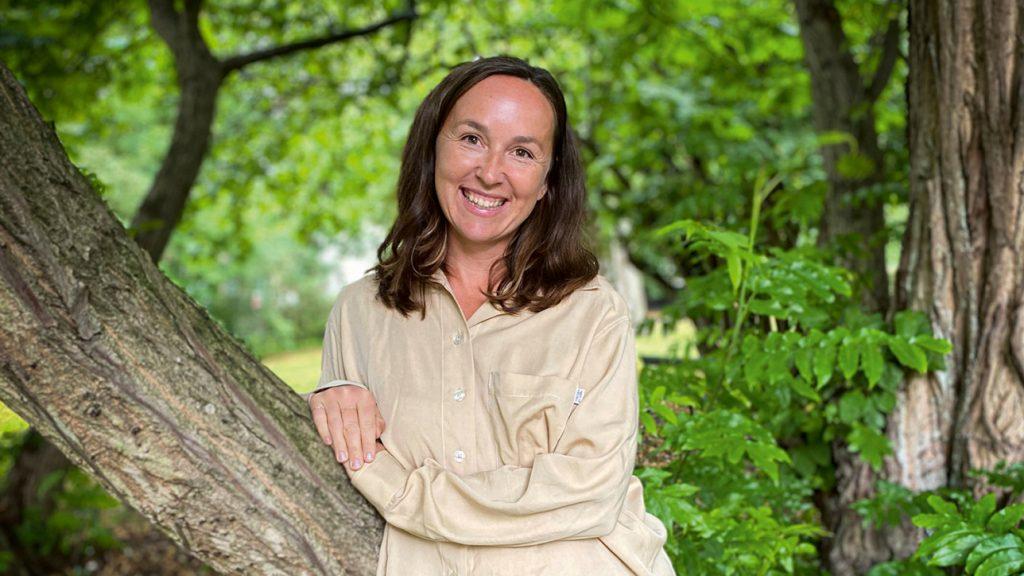 Bilden föreställer Anna Oudin som lutar sig mot en trädstam. Bilden är förmodligen tagen i en grönskande park.