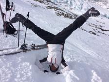 Bilden föreställer Carin Andrén Aronsson där hon står i en huvudstående yogaposition i snön i vad som ser ut att vara skidbacken. Bredvid henne syns ett par skidor och stavar.