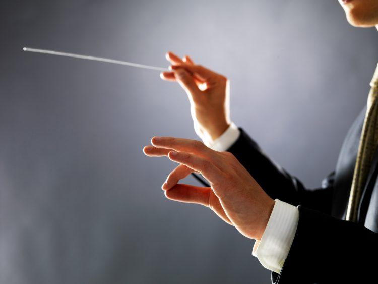 på bilden ses händerna på en dirigent som precis har lyft taktpinnen med höger hand