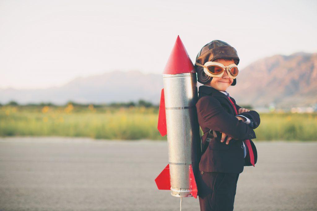 Bilden föreställer en liten pojke klädd i kavaj, gammaldags flygarluva och flygarglasögon. På ryggen har han en hemmabyggd raket . Han tittar in i kameran och ler. Han står på en asfalterad väg eller möjligen ett asfalterat flygfält
