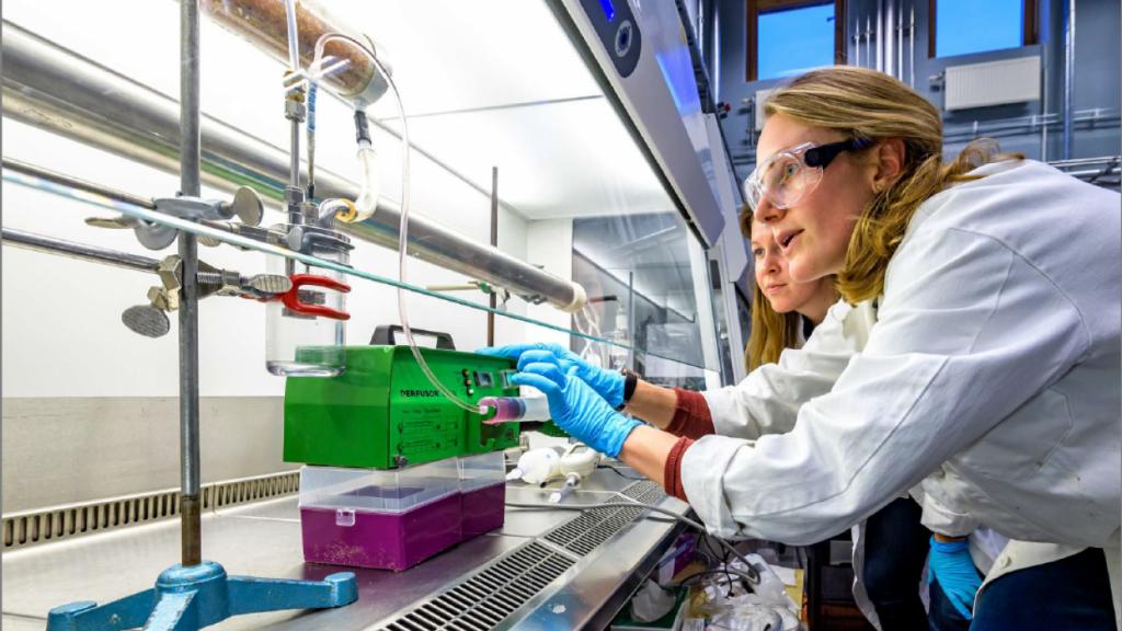 På bilden ses Malins Alsved iklädd vit labbrock och skyddsglasögon framför ett dragskåp. I dragskåpet syns några lådor. Bakom Malin skymtar en annan person.