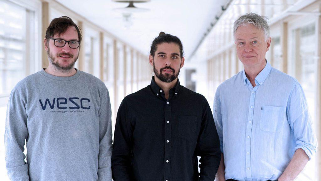 Bild på forskarna Johan Agorelius, Alexander Dontsios Holmkvist och Jens Schouenborg. De står bredvid varandra i en korridor.