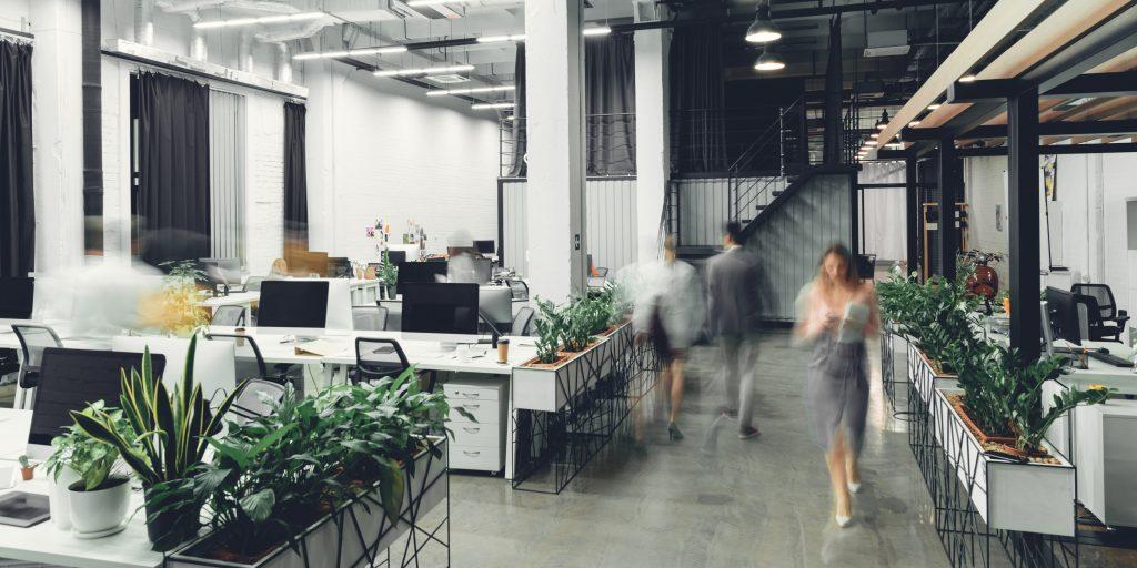 Bilden är ett exempel på så kallad aktivitetsbaserad arbetsplats. Det är en ganska stor öppen lokal där olika grupper av arbetsplatser finns utspridda i lokalen. Det finns inga avskärmningar eller väggar mellan arbetsplatserna. Arbetslokalen delas av en gång och där ses tre personer som går. De är suddiga vilket ska föreställ rörelse.